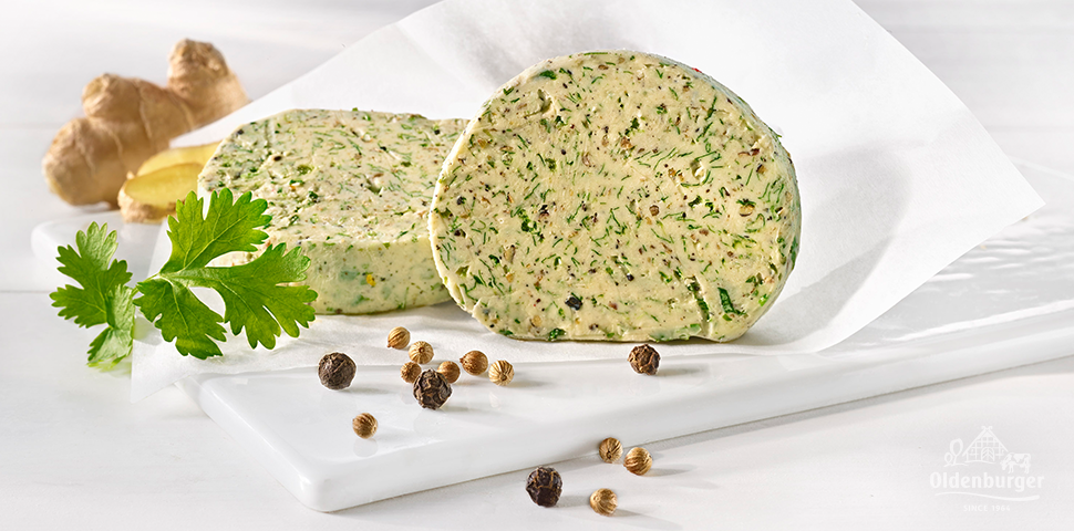 Slices of spiced butter on a plate decorated with pepper, parsley and ginger.